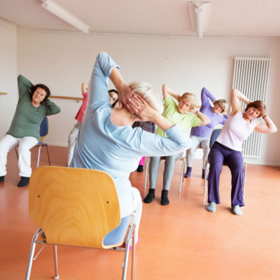 A chair exercise group stretching.