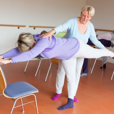 An instructor assisting a woman participating in chair yoga.