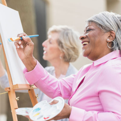Women painting on an easel.
